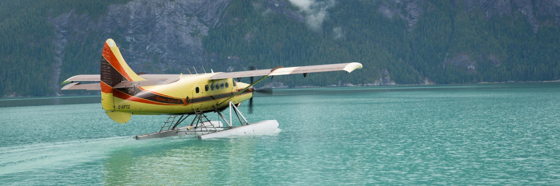 A float plane landed on the water near a mountain range