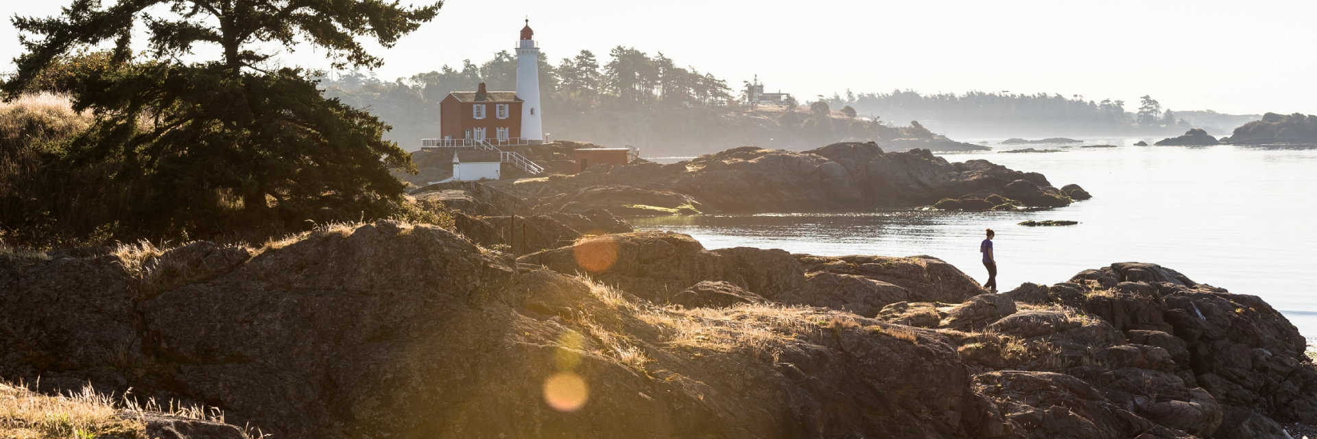 A person hiking on the rocks near Fisgard Lighthouse National Historic Site