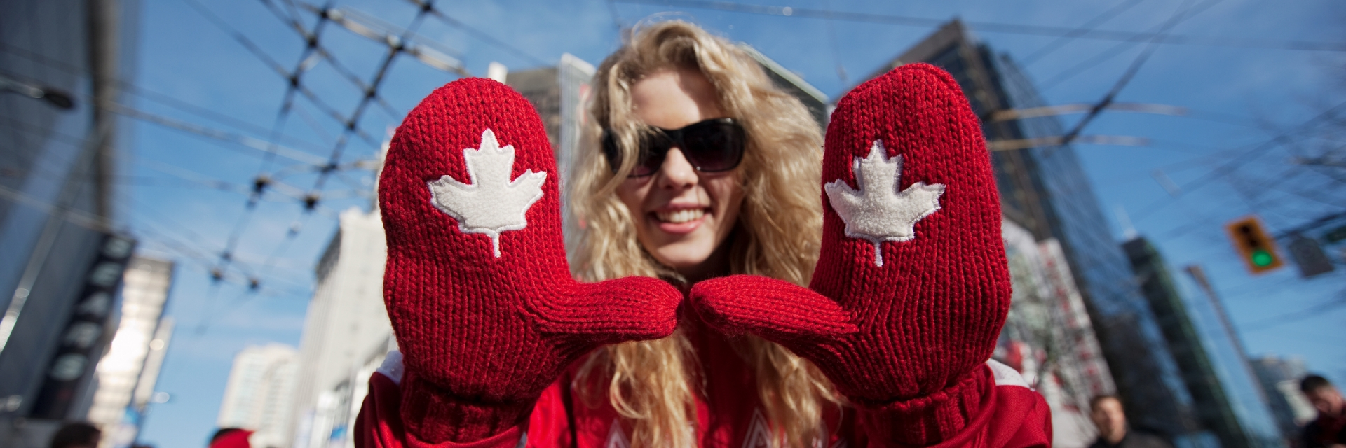 A woman with gloves with Canadian maple leafs on them.