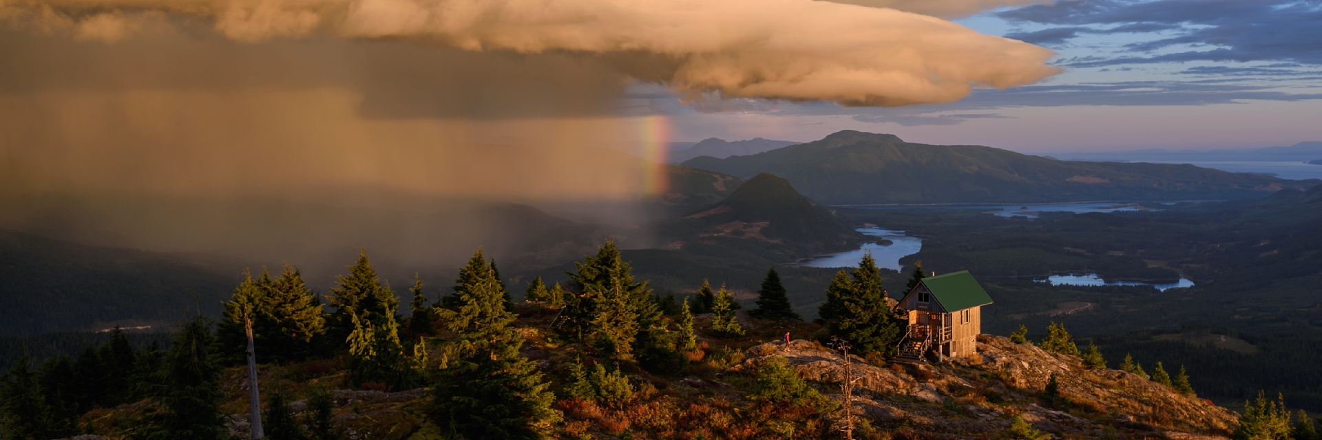 A storm front passes by Tin Hat Mountain producing a spectacular rainbow over the Tin Hat Hut.