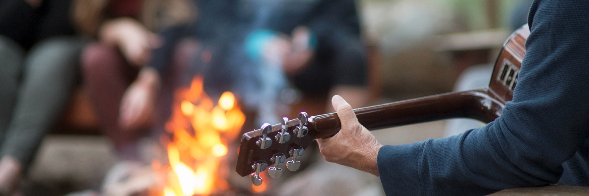A guitar player performing for a group around a fire.