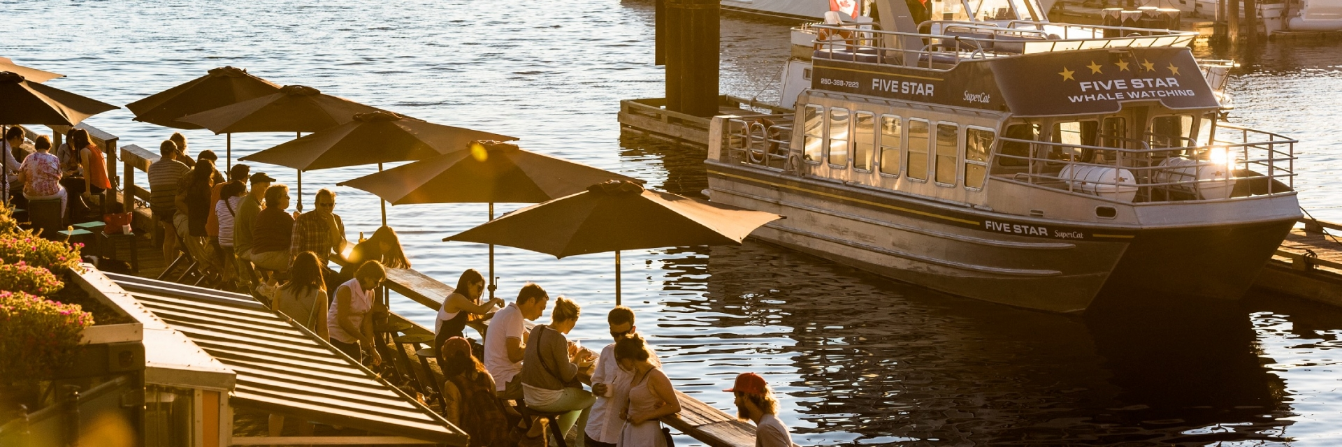 People enjoying food on the patio overlooking the marina in Victoria's Inner Harbour