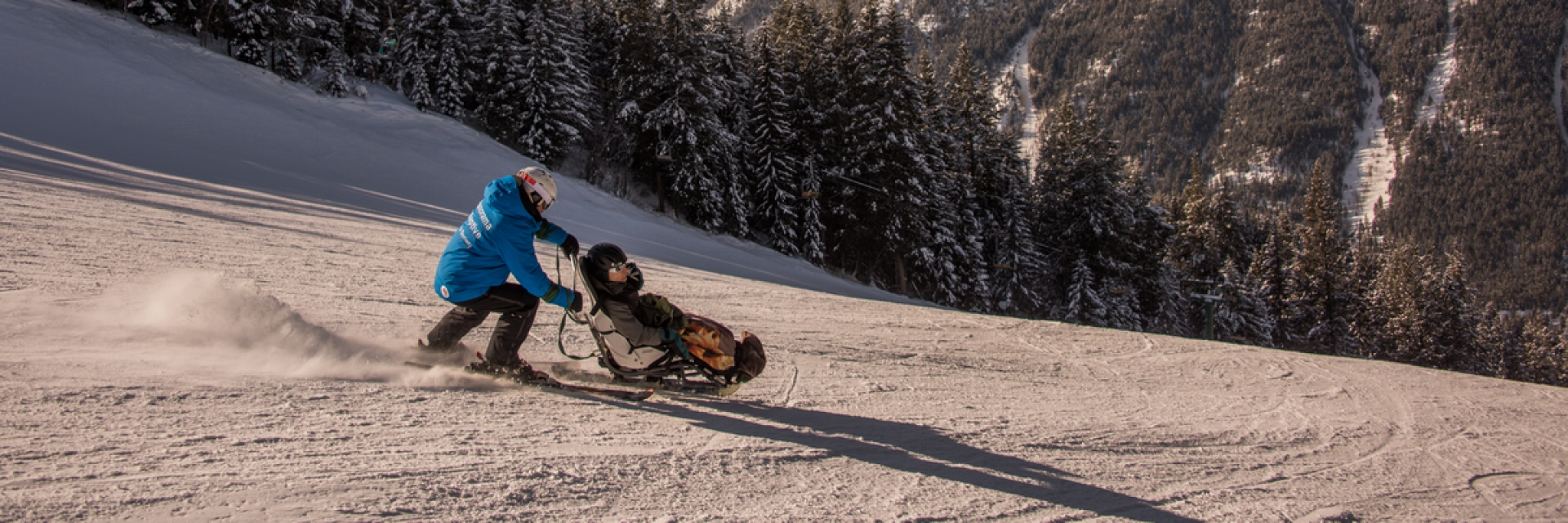 A person pushing another in an accessible skiing wheelchair
